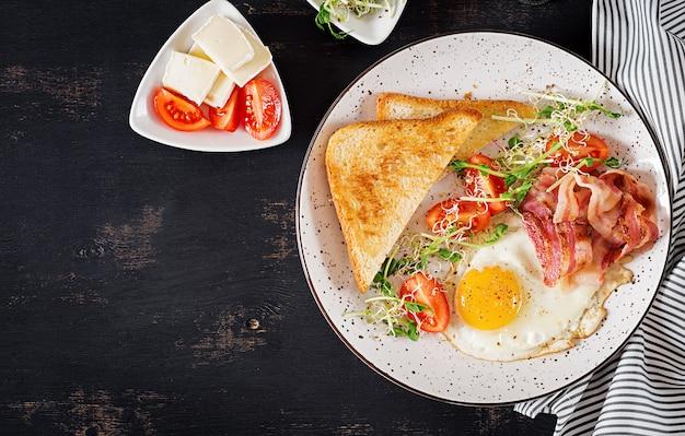 Toast, ei, bacon en tomaten en microgreensalade.