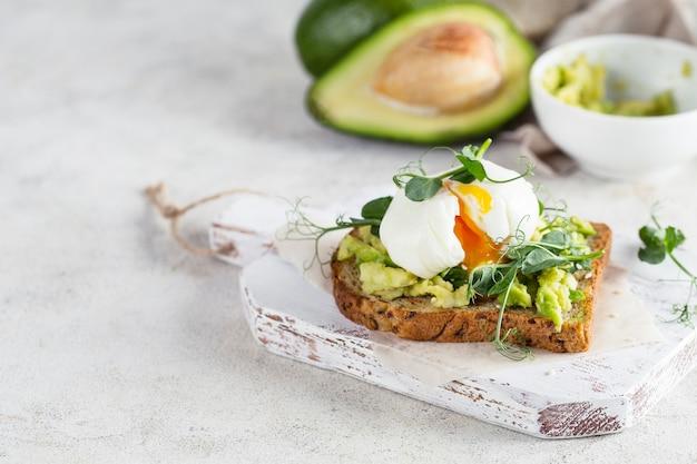 Toast gepocheerd ei avocado op wit bord