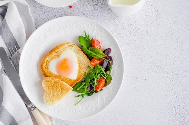 Toast in de vorm van een hart met ei op een witte plaat met rucola en kerstomaatjes