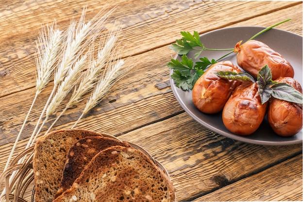 Toast in rieten mand en gegrilde worstjes met basilicum en peterselie op plaat. bovenaanzicht met oren van tarwe en houten planken op de achtergrond..