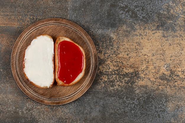 Toast met aardbeienjam en zure room op een houten bord.
