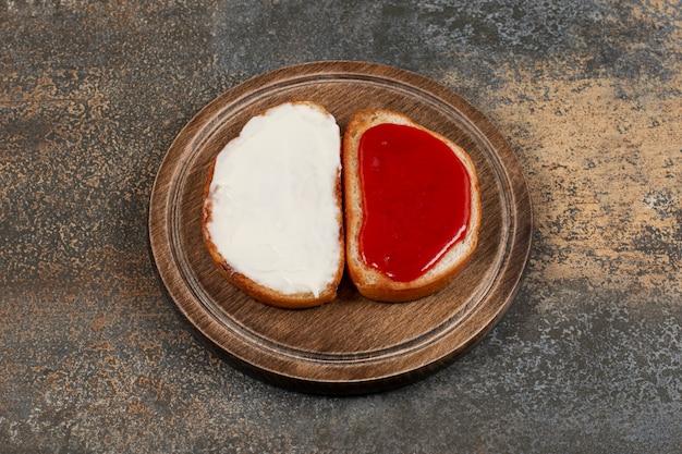 Toast met aardbeienjam en zure room op houten bord.