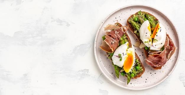 Toast met avocado, asperges en benedict gepocheerde eieren met prosciutto