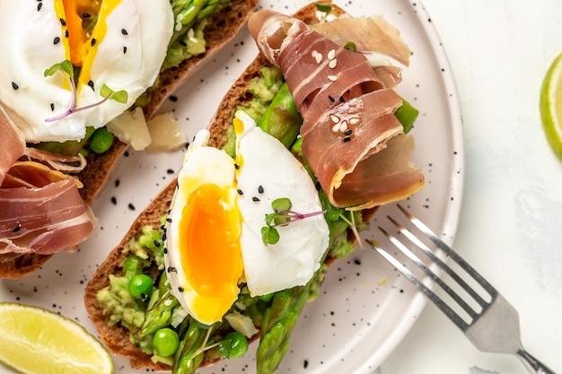 Toast met avocado, asperges en benedict gepocheerde eieren