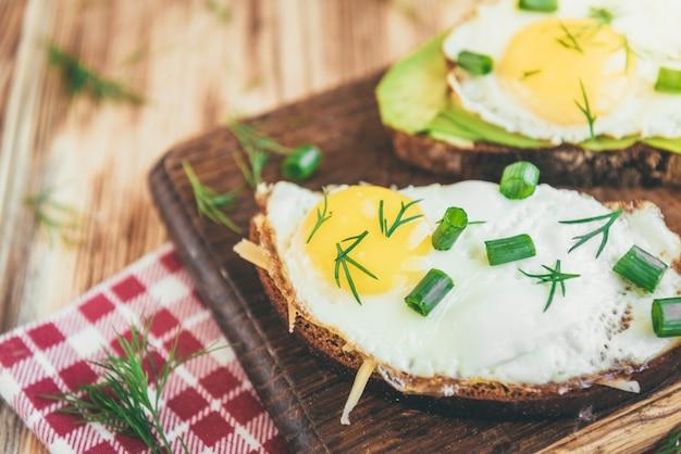 Toast met avocado, eieren, groene ui en kaas op houten snijplank.