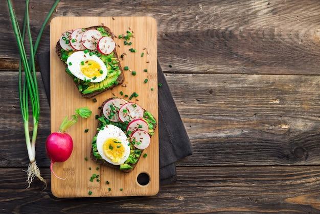 Toast met avocado, eieren, radijs, groene ui en lijnzaad op rustieke houten achtergrond. bovenaanzicht. kopieer ruimte gebied.
