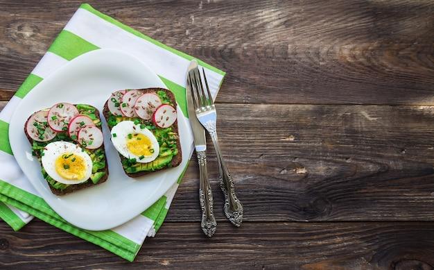 Toast met avocado-eieren, radijs, groene ui en lijnzaad op rustieke houten achtergrond bovenaanzicht