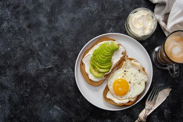 Toast met avocado en gebakken ei als ontbijt.