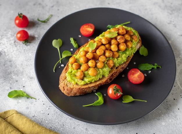 Toast met avocado, geroosterde kikkererwten, kerstomaatjes, kruiden op een donkere plaat gezond veganistisch voedsel grijs betonnen oppervlak