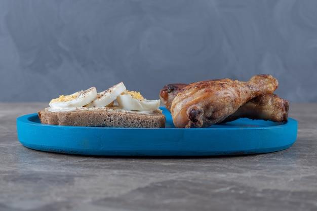 Toast met eieren en kip drumsticks op blauw bord.