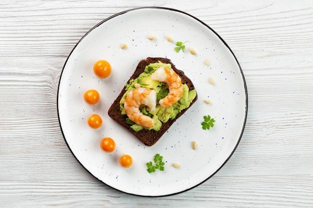 Toast met garnalen, avocado, noten, physalis, peterselie op plaat