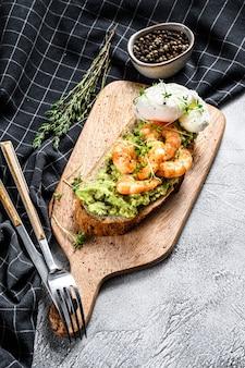 Toast met garnalen, garnalen, avocado en gepocheerd ei. bovenaanzicht