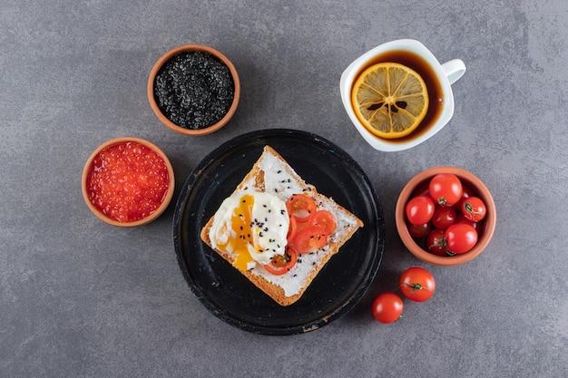 Toast met gebakken ei en een kopje zwarte thee op stenen tafel.