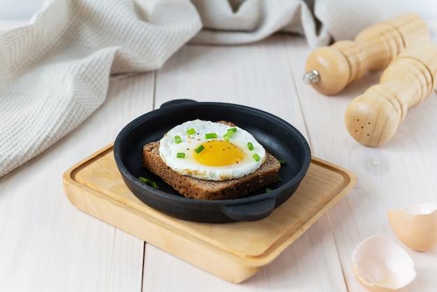 Toast met gebakken ei en groene uien in een gietijzeren koekenpan