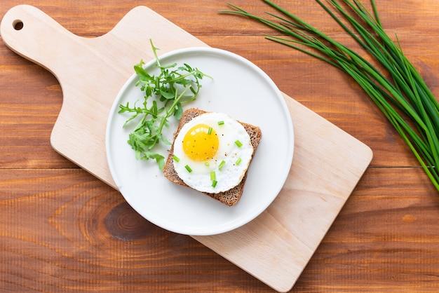 Toast met gebakken ei, groene uien en rucola in een bord op een houten plank