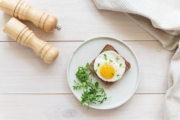 Toast met gebakken ei-ui en rucola in een bord op een houten tafel