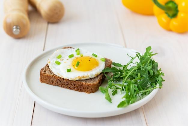 Toast met gebakken eieren met groene uien, rucola en kruiden in een bord op een houten tafel