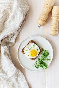 Toast met gebakken eieren met groene uien, rucola en kruiden in een bord