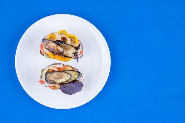Toast met gebakken groenten op witte plaat op blauwe ondergrond.