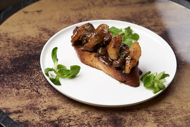 Toast met gebakken kippenlever op witte plaat op tafel. kippenlevertjes op toastbrood met kruiden