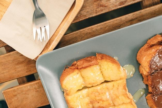 Toast met gecondenseerde melk en chocolade die op een lijst worden gediend.