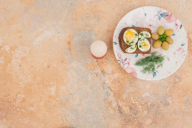Toast met gekookte eieren, olijven op witte plaat