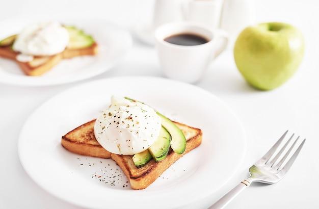 Toast met gepocheerde eieren en avocado. gezond ontbijt en eten. gezellige ochtend. voeding voor zwangere vrouwen. dieet voor vrouwen. ontbijt op hotelkamer of bed. sandwich met roerei.