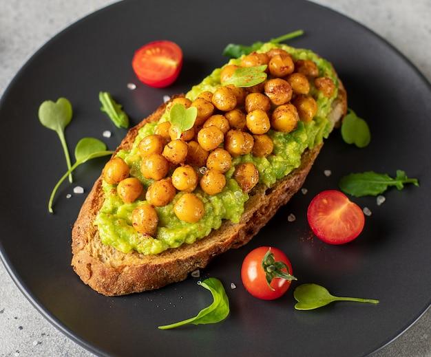 Toast met gepureerde avocado, geroosterde kikkererwten, cherry tomaten, kruiden op een donkere plaat gezond voedsel concept close-up