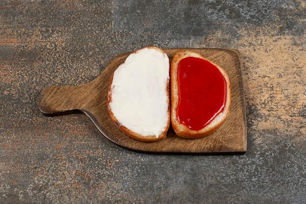 Toast met jam en zure room op houten bord.