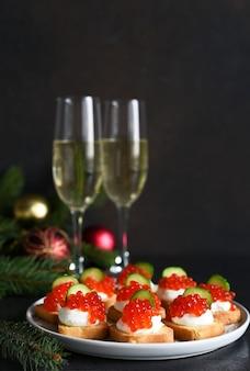 Toast met kaas en rode kaviaar op een new year's tafel met champagne. nieuwjaarstafel. tussendoortje.