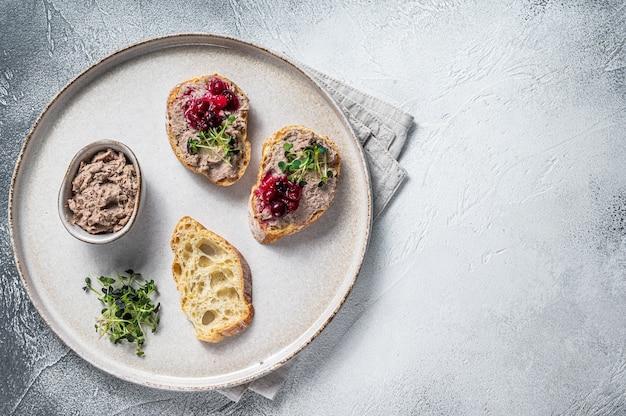 Toast met kip rillettes paté op wit brood met spruitjes. witte achtergrond. bovenaanzicht. ruimte kopiëren.