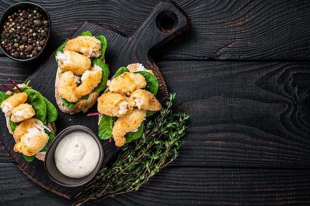 Toast met knapperige gebakken garnalen garnalen en groene salade op een houten bord. zwarte houten achtergrond. bovenaanzicht. kopieer ruimte.