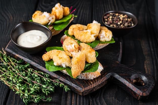 Toast met knapperige gebakken garnalen garnalen en groene salade op een houten bord. zwarte houten achtergrond. bovenaanzicht.