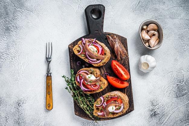 Toast met olijfolie, kruiden, tomaten en pittige ansjovisfilets. witte tafel. bovenaanzicht.