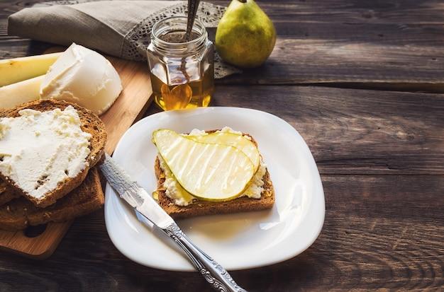 Toast met peer, ricotta en honing op rustieke houten met ingrediënten.