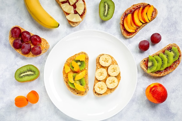 Toast met pindakaas, aardbeienjam, banaan, druiven, perzik, kiwi, ananas, noten