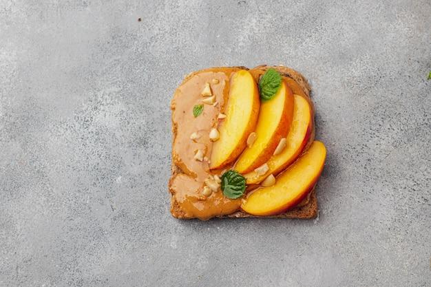 Toast met pindakaas, honing, munt, pinda en nectarine. flatlay met copyspace