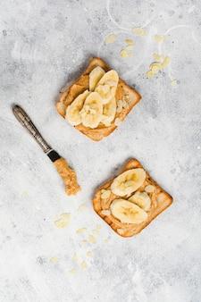 Toast met pindakaas, plakjes banaan, honing en amandelschilfers op oud grijs betonnen oppervlak