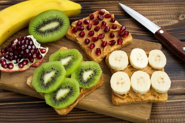 Toast met pindapasta en fruit op de snijplank