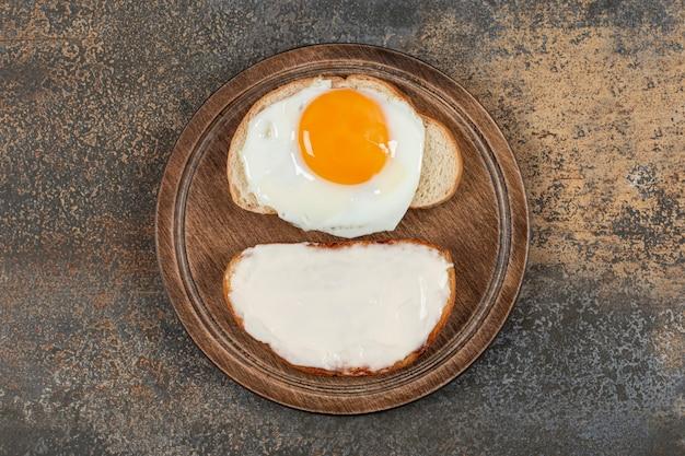 Toast met roomkaas en ei op een houten bord.