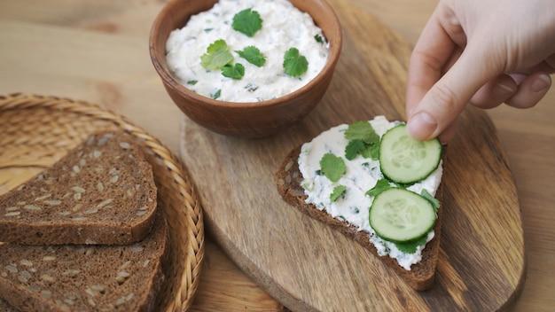 Toast met roomkaas en komkommer op houten bord