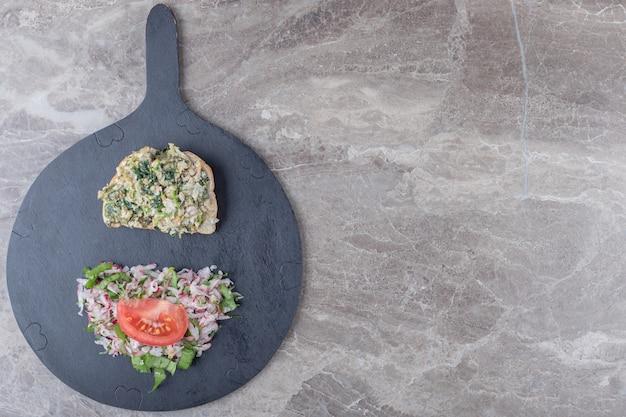 Toast met smakelijke salade op donker bord.