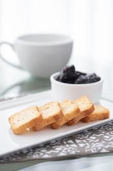 Toast met veenbessenjam en een kop van koffie op wit