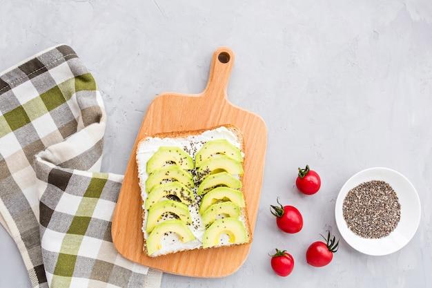 Toast met verse avocado, roomkaas en chiazaad op grijs beton