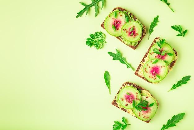 Toast met watemeloen radijs avocado en flex zaden op kleur achtergrond bovenaanzicht