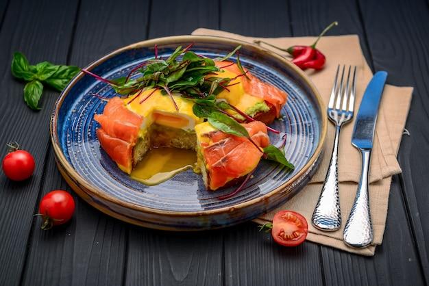 Toast met zalm, gepocheerd ei en avocado op een bord. ontbijt in het restaurant