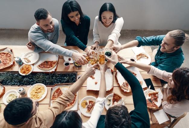 Toast op vrienden! bovenaanzicht van jonge mensen in vrijetijdskleding die elkaar roosteren en glimlachen tijdens een etentje binnenshuis
