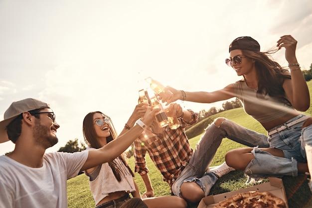Toast op vrienden! groep jonge lachende mensen in vrijetijdskleding proosten op elkaar terwijl ze genieten van een picknick op een warme zomerdag in de buitenlucht