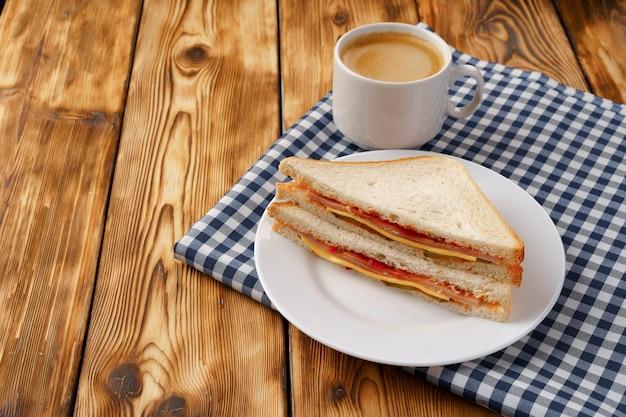 Toast sandwich in plaat en kopje koffie op servet op houten tafel