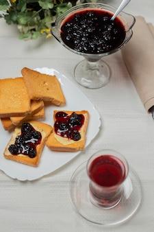 Toast voor het ontbijt met aardbeienjam en een glas thee